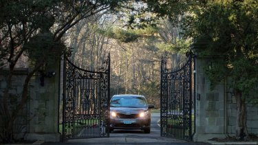 Cars with diplomatic plates drive out of a compound near Glen Cove on Long Island on December 30, after the US expelled dozens of Russian diplomats.