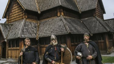 Anders Kvale Rue, centre, who leads a group of amateur Viking enthusiasts, with his friends Oystein Rivrud, right, and Rivrud's son Nils, left, in front of a 13th century church in Heddal, Norway.