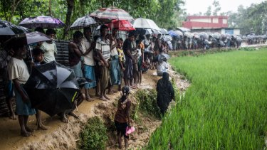 Rohingya refugees queue for hours, waiting for an aid distribution, in Bangladesh.