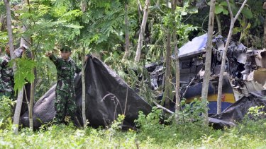 Indonesian soldiers try to cover the wreckage of the Indonesian Air Force's T-50 Golden Eagle plane which crashed during an air show in Yogyakarta on Sunday.