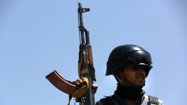 An Afghan security policeman stands guard near the site of a truck bombing earlier this year.