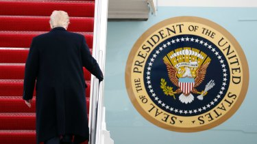 US President Donald Trump walks up the steps of Air Force One.