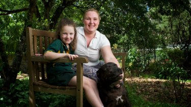Breast cancer sufferer Melanie Cage relaxes at her home in Lawson with her daughter Shaylee and dog Max.