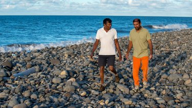 Johnny Begue, right, who found the plane debris, on the beach at Saint-Andre, with his friend Andre Tevane,