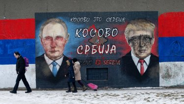 People walk by Serb nationalist graffiti depicting Russian President Vladimir Putin, left, and US President Donald Trump in Belgrade.