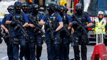 Armed police officers patrol streets near the scene of the terror attack in London.