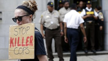 A protester displays a sign outside the courthouse in Baltimore.