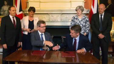 DUP MP Jeffrey Donaldson, sitting left, and government chief whip Gavin Williamson shake hands on the deal.