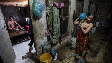 Poor Cambodia: A woman washes herself outside a tiny room where she lives with four other family members off a dank alleyway near the Phnom Penh factory where she works.