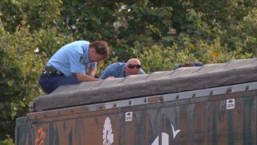 Police look into the back of the sand-blowing truck, where the man's body was found.