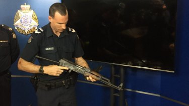 A Victoria Police ballistics officer with a firearm seized this year.