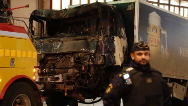 A destroyed truck is pull away by a service car after it was driven into a department store in Stockholm, Sweden.