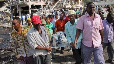 Somalis remove the body of a man killed in Saturday's blast, in Mogadishu.