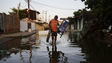 Saturnino Zorrilla carries chairs from his flooded home to a shelter in Asuncion, Paraguay. The Paraguay River is at its highest level since 1984.