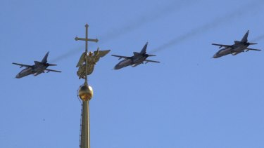 Sukhoy SU-24M military jets fly over a gilded weather vane in the form of an angel, fixed atop a spire of the Saints Peter and Paul Cathedral during a Naval parade rehearsal in St.Petersburg, Russia.
