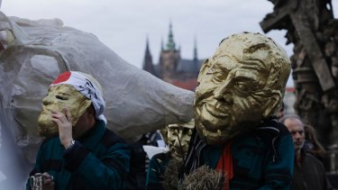 A man in a mask depicting Milos Zeman marches during commemorations for the anniversary of the Velvet Revolution.