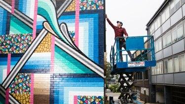 Street artist Bradley Eastman, aka Beastman, spray-paints a two-storey mural in St Leonards.