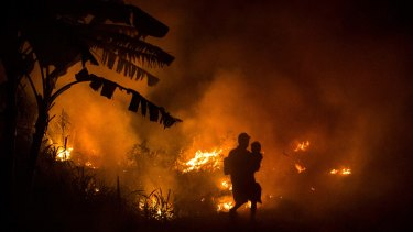 A man carries his son past a fire at Ogan Ilir district in South Sumatra, Indonesia.