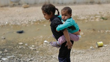 A Syrian refugee girl holds her brother at the al-Marj camp. Child labour is a growing problem.