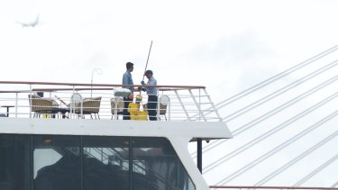 Crew members of the P&O's newly-launched cruise liner Pacific Eden clean and disinfect the ship while docked at the White Bay terminal.