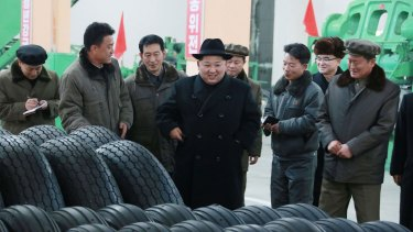 North Korean leader Kim Jong-un, centre, visits a local tire factory in Chagang Province to thank workers who built the tires for a huge vehicle used to transport the ballistic missile tested last week.