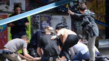 Witnesses help the injured on Bourke Street.