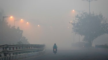 A man rides a scooter on a road enveloped by smoke and smog in Delhi, India on October 31, 2016.