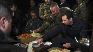 Syrian President Bashar al-Assad, right, eats with soldiers during a visit to Jobar, northeast of Damascus, in this handout photograph distributed by Syria's national news agency SANA on Thursday.