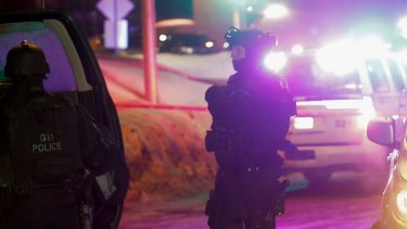 Police survey the scene after a deadly shooting at a mosque in Quebec City, Canada on Sunday.