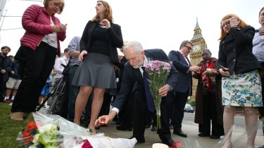 Labour Party leader Jeremy Corbyn, centre, lays a candle at an impromptu vigil at Parliament Square.