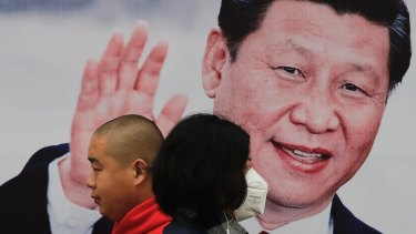 Pedestrians, one wearing a mask, walk by a poster of Chinese President Xi Jinping on a street in Beijing.