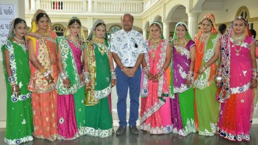 Savani with brides last year at his Surat school where the mass weddings take place.