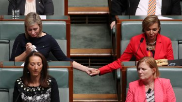 Susan Lamb holds hands with Anne Aly as Opposition Leader Bill Shorten delivered a statement about the death of Linda Burney's son in October.