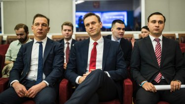 Alexei Navalny, centre, who submitted endorsement papers necessary for his registration as a presidential candidate, centre, waits for the decision.