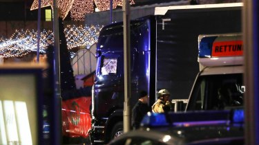 Police stand beside a damaged truck which ran into crowded Christmas market in Berlin.