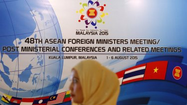 A woman waits to greet delegates of the 48th ASEAN foreign ministers meeting in Kuala Lumpur, Malaysia.