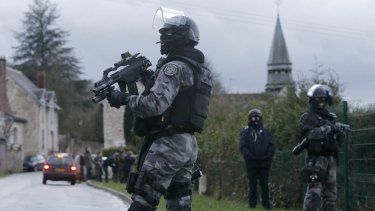 Hunting for terror suspects: Member of the French GIPN intervention police force secure a neighbourhood in Corcy, north-east of Paris. It sits next to the town of Longpont, which has been surrounded by police, according to reports.