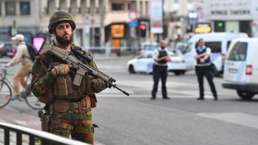 A Belgian Army soldier stands outside Brussels Central Station. While the risk of being caught in a terror attack remains low, the perception of the public - and tourists - is another matter.