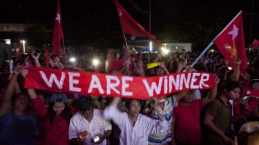 Hopeful supporters of Aung San Suu Kyi's National League for Democracy party anticipate the result of general election outside the party's headquarters on Sunday.