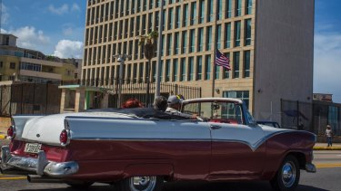 Tourists ride a classic convertible car on the Malecon beside the United States Embassy in Havana, Cuba.