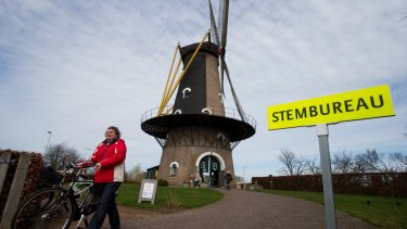 A woman leaves after casting her vote at the Kerkhovense Molen, a windmill turned polling station in Oisterwijk, south central Netherlands.