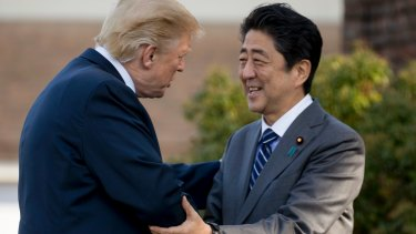President Donald Trump greets Japanese Prime Minister Shinzo Abe at Kasumigaseki Country Club in his first trip to Asia.