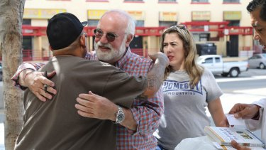'They discover they are the hero of their own story': Greg Boyle gets a hug from a staffer in Los Angeles.