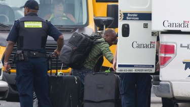 A man removes his belongings from a truck at a processing centre for asylum seekers at the Canada-United States border in Lacolle, Quebec.