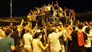 People gather on top of a Turkish army tank at Ataturk Airport in Istanbul.