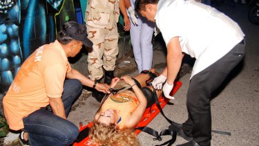 Rescue workers help an unidentified woman after one of the Hua Hin blasts earlier this month.