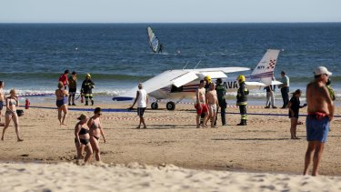 People walk past a small plane resting on the beach at Sao Joao beach at Caparica in Portugal.