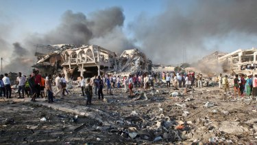 Somalis gather and search for survivors by destroyed buildings at the scene of a blast in Mogadishu, Somalia.