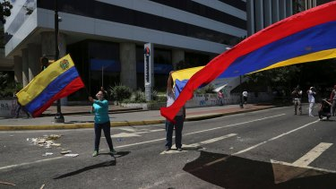 Anti-government demonstrators wave Venezuelan national flags during a protest against Venezuela's President Nicolas Maduro in Caracas, Venezuela.