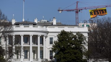 "Greenpeace activists hang a banner off of a construction crane that reads ""Resist"" past the White House in Washington, DC."